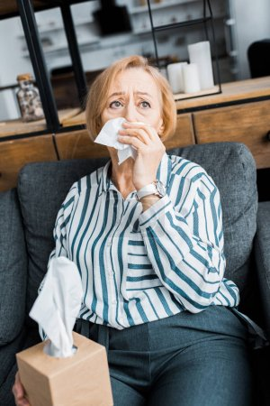 Photo pour Femme âgée malade avec nez qui coule tenant des tissus et souffrant de froid à la maison - image libre de droit