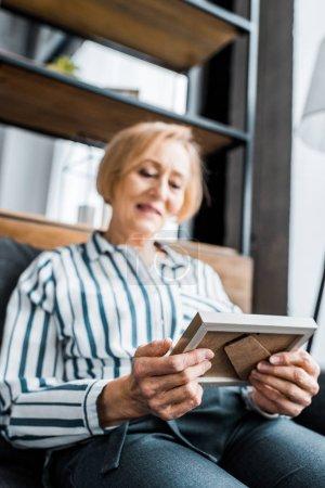 Seniorin in legerer Kleidung sitzt und schaut auf Bilderrahmen