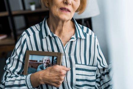 Foto de Vista parcial de mujer senior marco con hombre en fotografía en casa - Imagen libre de derechos