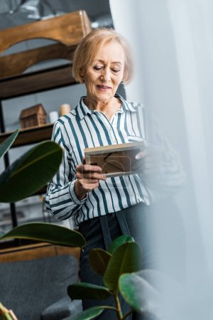 Foto de Enfoque selectivo de senior mujer mirando el cuadro en casa - Imagen libre de derechos