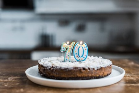 Photo for Selective focus of delicious birthday cake with burning candles and '70' sign on top - Royalty Free Image