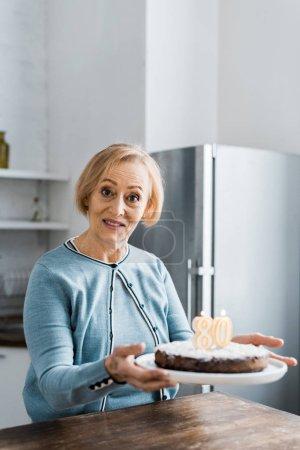 """Photo pour Haute femme regardant la caméra et la tenue de gâteau avec le signe """"80"""" sur le dessus au cours de la célébration de l'anniversaire - image libre de droit"""