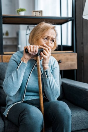 Photo for Upset senior woman holding walking stick, covering mouth with hand and crying at home - Royalty Free Image