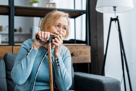Photo for Upset senior woman holding walking stick, covering mouth with hand and crying at home with copy space - Royalty Free Image