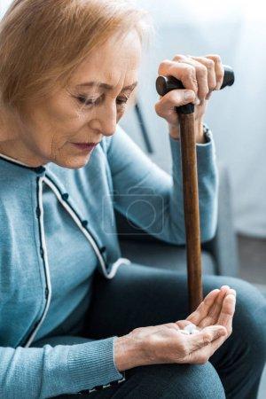 Photo pour Femme senior malade avec canne tenant la médecine dans la main - image libre de droit