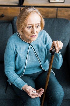 Photo pour Femme senior malade avec canne assis sur le canapé et la tenue de la médecine dans la main - image libre de droit