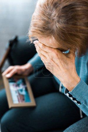 mujer mayor cubriendo la cara con la mano y llorando mientras mira el marco de la foto