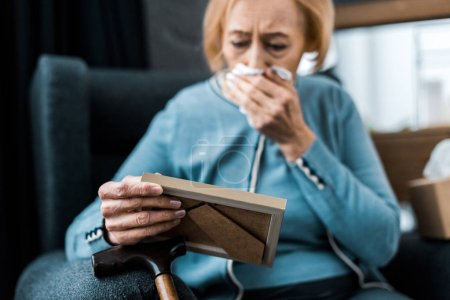 Photo for Grieving senior woman crying and wiping face from tears with tissue while looking at picture frame - Royalty Free Image