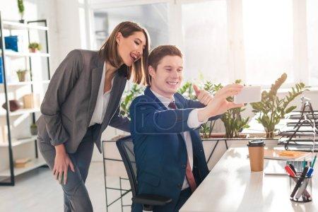 Photo pour Jolie femme montrant la langue près souriant collègue d'exploitation smartphone et prise selfie dans bureau - image libre de droit