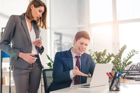 Photo for Attractive businesswoman standing with smartphone near coworker gesturing while watching video on laptop - Royalty Free Image
