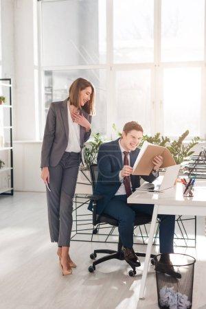 Photo pour Femme d'affaires attrayant debout avec smartphone proche collaborateur heureux en riant tout en regardant les documents au bureau - image libre de droit