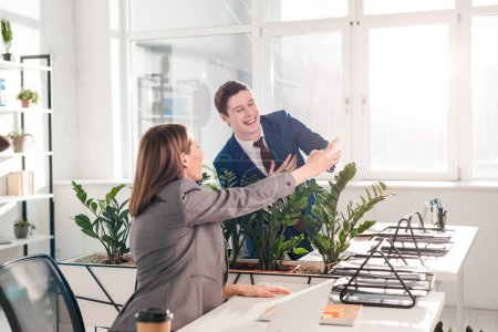 Photo pour Femme d'affaires détenant smartphone et rire avec une collègue au bureau - image libre de droit