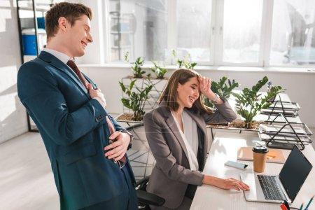 Photo pour Femme d'affaires joyeuse riant avec collègue près de l'ordinateur portable dans le bureau - image libre de droit