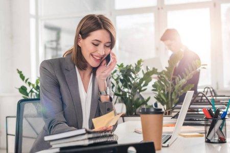 Photo pour Foyer sélectif de femme d'affaires gaie regardant des notes collantes tout en parlant sur smartphone avec collègue en arrière-plan - image libre de droit