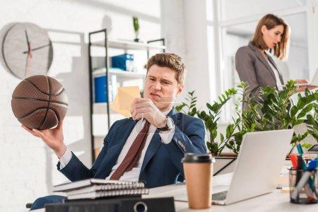 Photo pour Mise au point sélective d'homme d'affaires insatisfait en regardant les notes collantes tout en maintenant le basket-ball en bureau avec collègue sur le fond, le concept de la procrastination - image libre de droit