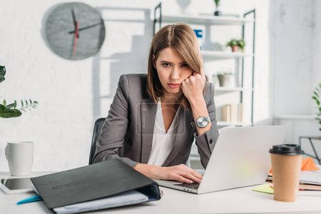 Photo for Exhausted businesswoman looking at camera while sitting near laptop in office - Royalty Free Image
