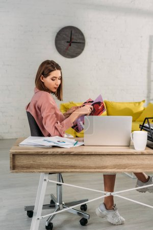 attractive woman holding magazine near laptop at home
