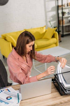 Photo pour Jolie femme à la recherche de documents dans le bac près de tableaux et de graphiques à la maison - image libre de droit