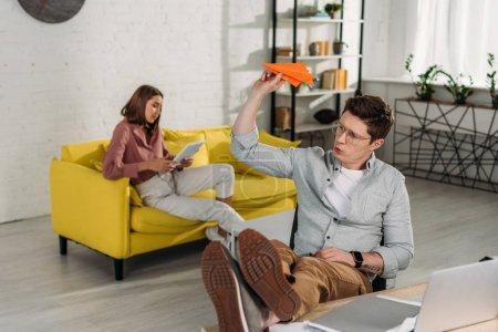 Photo pour Foyer sélectif de l'homme jouant avec avion en papier près d'un ordinateur portable avec petite amie sur fond - image libre de droit