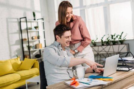 Photo pour Petite amie gaie riant près de petit ami gai pointant du doigt à l'ordinateur portable à la maison - image libre de droit
