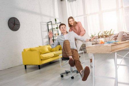 Photo pour Femme gaie souriant tout en poussant chaise de petit ami heureux dans des lunettes - image libre de droit