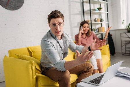 Photo pour Foyer sélectif de l'homme dans les lunettes geste près de l'ordinateur portable avec petite amie parler sur smartphone tout en étant assis sur le canapé sur fond - image libre de droit