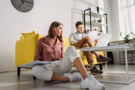Photo pour Attrayant femme tenant des documents et assis sur le sol près du petit ami assis sur le canapé - image libre de droit
