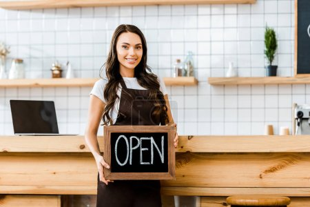Photo for Attractive cashier in brown apron standing near wooden bar counter and holding chalkboard with open lettering in coffee house - Royalty Free Image
