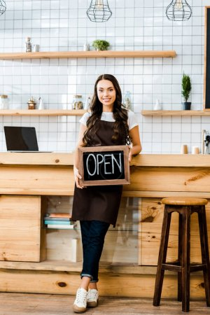 Photo for Beautiful cashier in apron standing near wooden bar counter and holding chalkboard with open lettering in coffee house - Royalty Free Image
