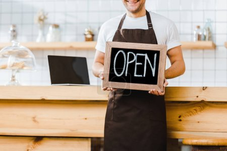Photo for Cropped view of cashier in apron standing near wooden bar counter and holding chalkboard with open lettering in coffee house - Royalty Free Image