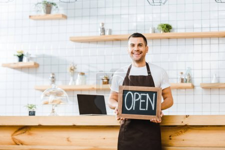 Photo for Handsome cashier in brown apron standing near wooden bar counter and holding chalkboard with open lettering in coffee house - Royalty Free Image
