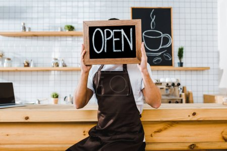 Photo for Cashier in apron sitting on chair near wooden bar counter and holding chalkboard in front of face with open lettering in coffee house - Royalty Free Image