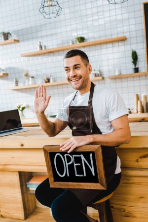 Photo for Handsome cashier in apron sitting on chair near wooden bar counter, holding chalkboard with open lettering and waving with hand in coffee house - Royalty Free Image