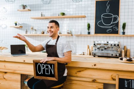 Photo for Handsome cashier in apron sitting near wooden bar counter, holding chalkboard with open lettering and greeting in coffee house - Royalty Free Image