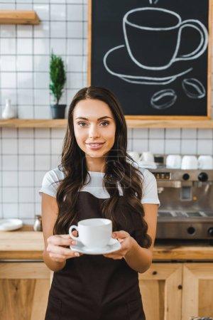 Photo pour Attrayant barista en tablier brun tenant tasse et soucoupe dans le café - image libre de droit