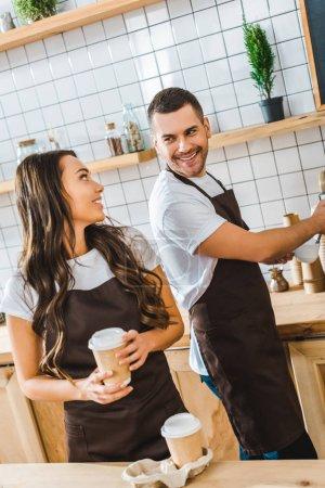Photo pour Barista en tablier brun faisant café et attrayant caissière brune tenant la tasse de papier dans la maison du café - image libre de droit