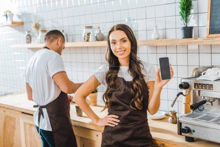 Photo pour Caissier de brunette séduisante indiquant un smartphone avec écran blanc wile barista travaille chez café - image libre de droit