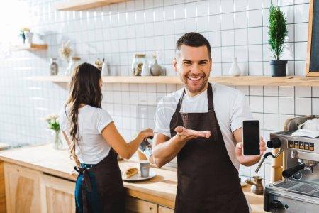 Photo pour Beau caissier pointant avec main sur smartphone avec écran blanc wile barista travaille chez café - image libre de droit