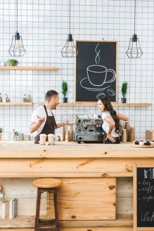 Photo pour Caissiers debout derrière comptoir, en parlant et en souriant dans la maison du café - image libre de droit
