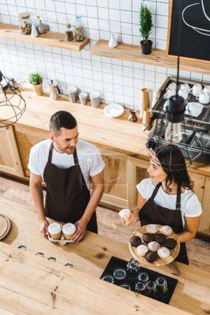 Photo for Attractive cashier with cupcakes and handsome barista with paper cups standing in brown aprons behind bar counter in coffee house - Royalty Free Image