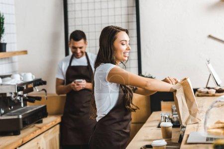 Photo pour Attrayant caissier en tablier brun emballage sac en papier wile barista regardant à smartphone près comptoir bar dans le café - image libre de droit