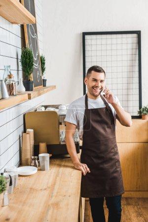 Photo pour Caissière beau brun tablier talking sur smartphone près de machine à café et bar comptoir de maison du café - image libre de droit