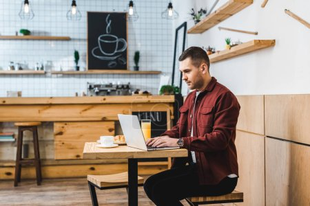 handsome freelancer sitting at table with laptop in coffee house