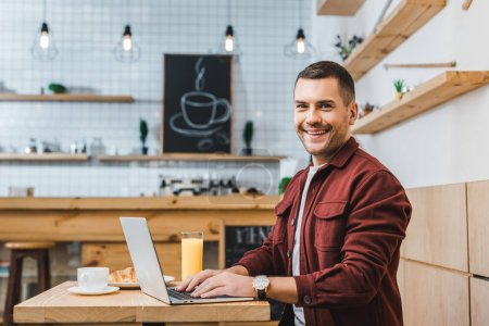 Photo for Handsome freelancer sitting at table with laptop and smiling in coffee house - Royalty Free Image
