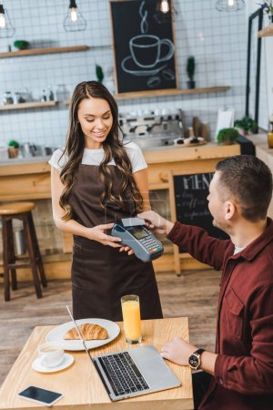 Photo for Attractive waitress holding terminal wile handsome man sitting at table with laptop and paying with credit card in coffee house - Royalty Free Image