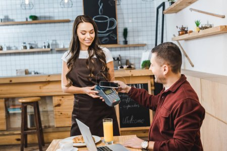 attractive waitress holding terminal wile handsome freelancer sitting at table with laptop and paying with smartphone in coffee house