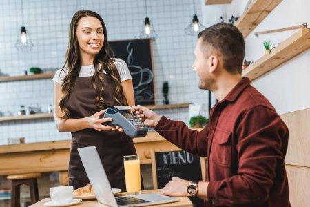 Photo pour Belle serveuse tenant terminal wile pigiste assis à table avec ordinateur portable et payer avec smartphone dans un café - image libre de droit