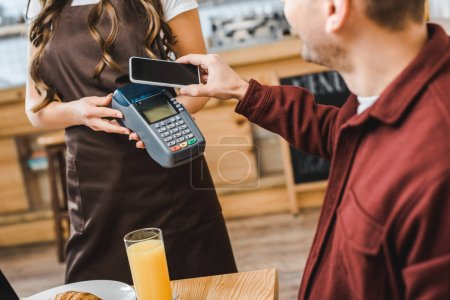 waitress view of barista holding terminal wile freelancer at table paying with smartphone in coffee house