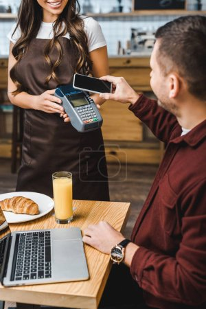 Photo for Waitress holding terminal wile freelancer at table paying with smartphone in coffee house - Royalty Free Image