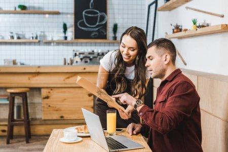 Foto de Hermosa mesera y sentarse a freelancer mesa mirando a menú y sonriendo en café - Imagen libre de derechos